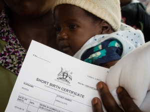 A mother shows off her baby's newly printed birth certificate soon after registering the birth at a hospital in central Uganda. ©UNICEF/Uganda/2013