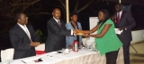 The Deputy Attorney General, Hon. Freddrick Ruhindi handing over the accolade for  Best Overall Employee of the Year (2013) to Ms Frances Katooko during the ULRC staff end of year  retreat on December 13 2013 at Colline Hotel, Mukono. Looking on is the Commission's Chairperson Prof. Agasha Mugasha (left)  and the Ag. Secretary Ms Sarah Nkonge (PHOTO:JLOS/ Gadenya Paul)