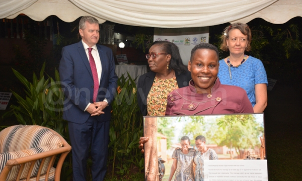 (Background left to right): William Carlos, the ambassador of Ireland to Uganda, Caroline Kego, a social development advisor at the embassy and Aine Doody, the head of co-operation, Irish embassy, pay tribute to Harriet Nabirye (foreground), a survivor of gender-based violence (PHOTO: New Vision)